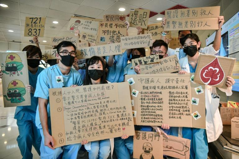 Medical staff holding placards in support of anti-government protesters lined the corridors of several Hong Kong hospitals (AFP Photo/Anthony WALLACE)