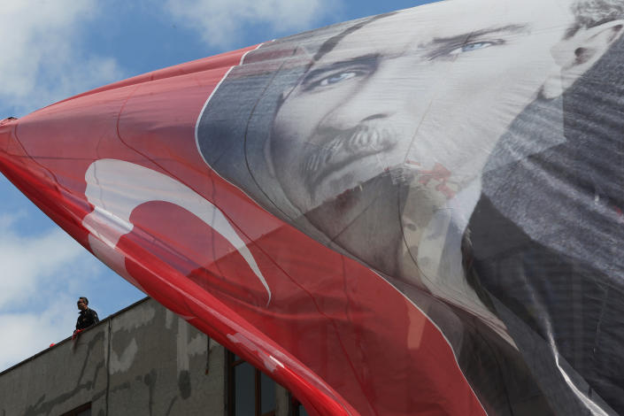 With a banner of Turkish Republic founder Mustafa Kemal Ataturk on the foreground, a Turkish police officer mans a rooftop during a rally of Turkey's President Recep Tayyip Erdogan in Istanbul, Friday, March 29, 2019, ahead of local elections scheduled for March 31, 2019. Erdogan has been holding multiple daily rallies across the country, using highly polarising language, portraying the opposition as traitors who are supported by terrorists, blaming ills on foreign forces and stirring up nationalist and religious sentiments. (AP Photo/Lefteris Pitarakis)