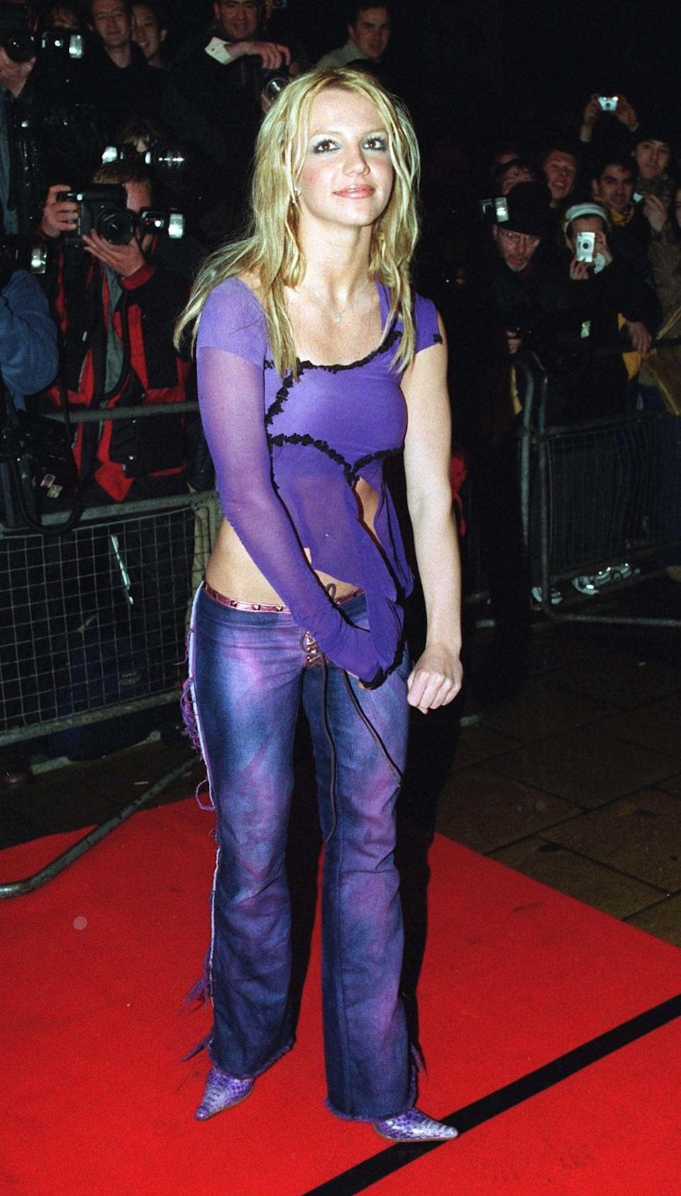 <p>At a party in London wearing a sheer purple cutout top with matching pants and shoes. </p>
