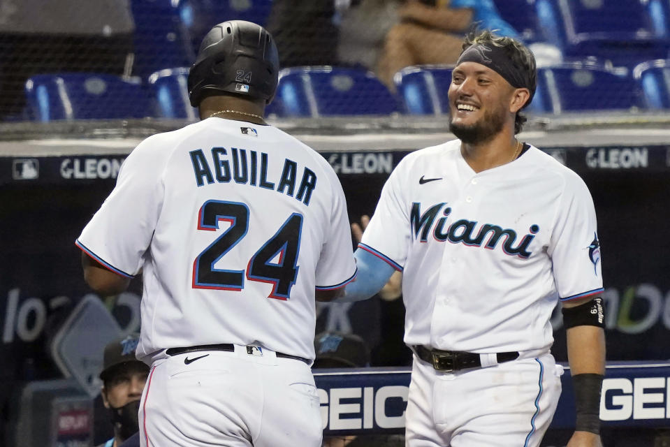 Miami Marlins' Miguel Rojas, right, and Jesus Aguilar (24) congratulate each other after scoring during the fifth inning of a baseball game against the Baltimore Orioles, Wednesday, April 21, 2021, in Miami. (AP Photo/Marta Lavandier)
