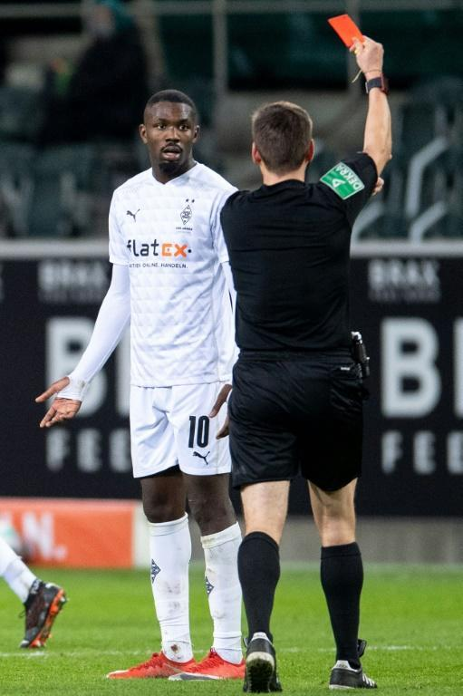 Moenchengladbach forward Marcus Thuram is shown a red card for spitting in an opponent's face