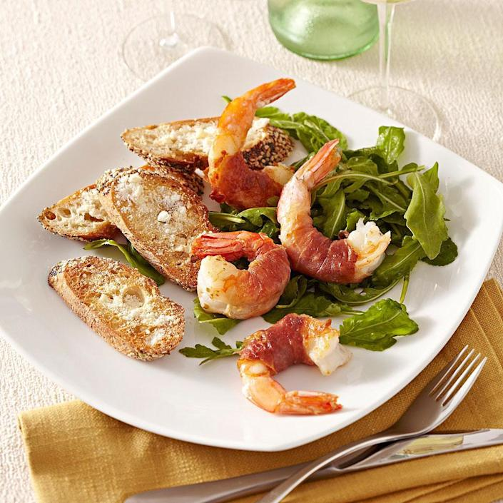 "<p>This recipe for jumbo shrimp wrapped in thin strips of prosciutto and served on a lemony bed of arugula is a practically effortless dish that's sure to impress your guests. Wrap your shrimp and make the dressing ahead of time, and you'll have dinner on the table even faster. Serve with toasted whole-wheat baguette sprinkled with Parmesan cheese. <a href=""http://www.eatingwell.com/recipe/250597/prosciutto-wrapped-shrimp-with-arugula-salad/"" rel=""nofollow noopener"" target=""_blank"" data-ylk=""slk:View recipe"" class=""link rapid-noclick-resp""> View recipe </a></p>"
