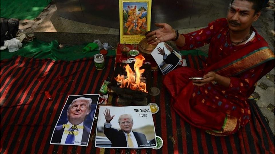 An Indian Hindu priest performs a Hawan (The Sarced Fire) ritual alongside posters bearing the image of US Republican presidential candidate Donald Trump in New Delhi on May 11, 2016.