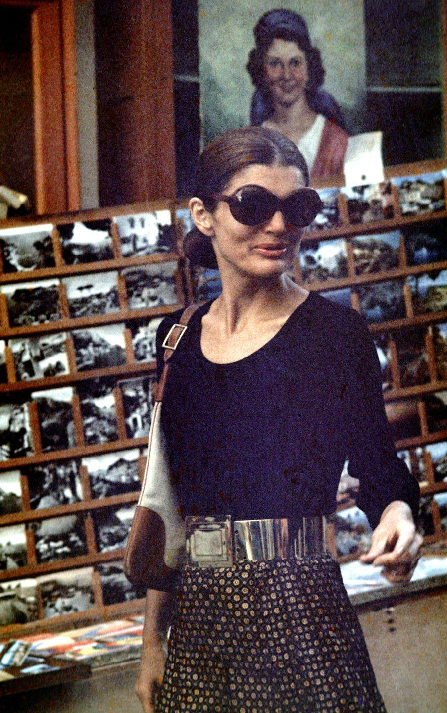 <p>Jackie next-levels her Italian vacation by channeling the style of Milan while shopping in Capri. Here, a chic black top, oversize metal belt, and patterned pants come together for a polished ensemble. <br></p>