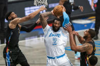 Los Angeles Lakers center Andre Drummond (2) grabs a rebound between Brooklyn Nets forward Bruce Brown, left, and center LaMarcus Aldridge during the first half of an NBA basketball game Saturday, April 10, 2021, in New York. (AP Photo/Corey Sipkin)