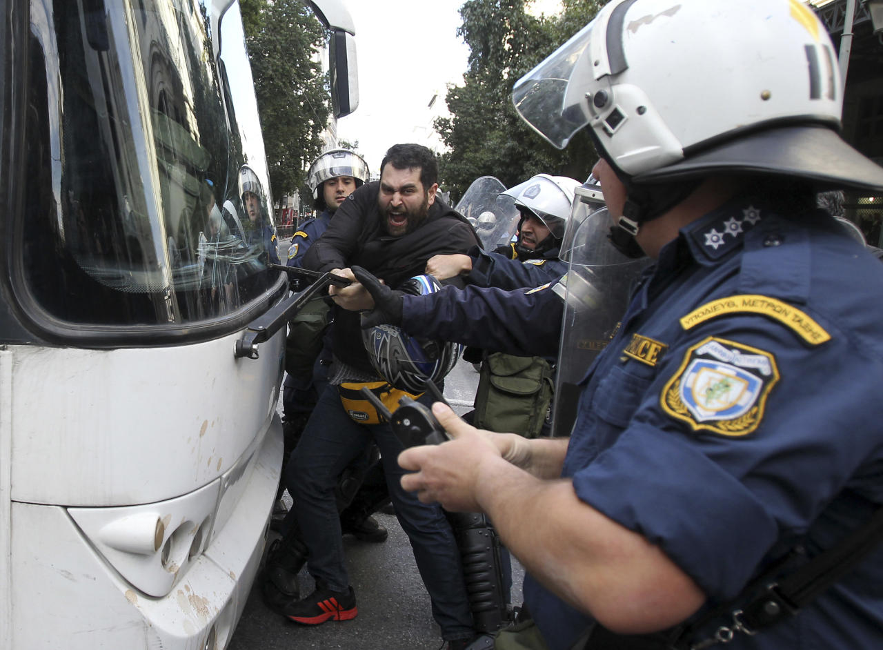 A man tries to stop the bus from driving away carrying detained protesters as riot police pull him away, during a protest outside the Labor Ministry in Athens, Wednesday, Jan. 30, 2013. Protesters from a Communist-back labor union forced their way into a government building and clashed with police who used tear gas to expel them. Members of the union are protesting planned reforms to the country's pension and income contribution system, part of ongoing austerity cuts demanded by Greece's euro partners and the International Monetary Fund who are keeping the country afloat with emergency loans. (AP Photo/Thanassis Stavrakis)