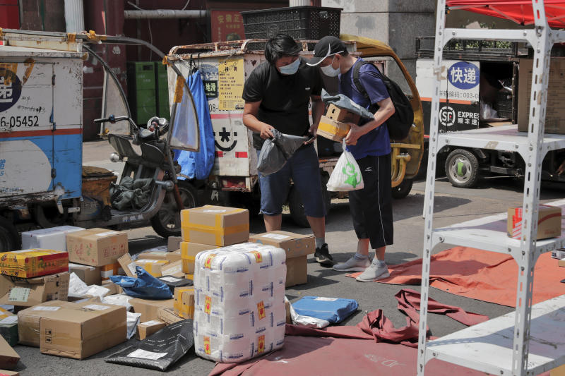 A delivery worker wearing a protective face mask to help curb the spread of the new coronavirus sorts out parcels for his customer at a collection point outside an apartment in Beijing, Sunday, June 21, 2020. According to state media reports, nearly one hundred thousand delivery workers have to accept the nucleic acid testing, a countermeasure to prevent the spread of the virus in the capital city. (AP Photo/Andy Wong)