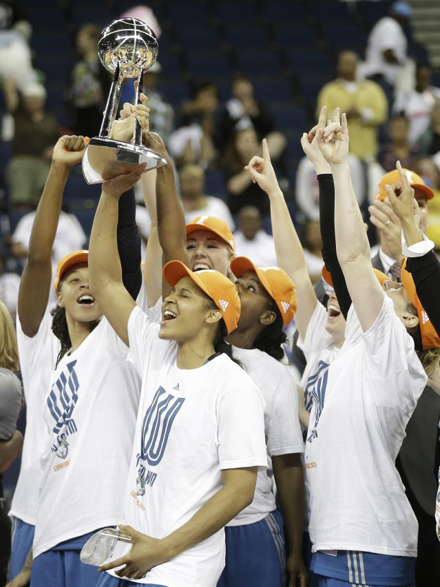 Minnesota Lynx' Maya Moore, second from left, holds the championship trophy with teammates after the second half of Game 3 of the WNBA Finals basketball series against the Atlanta Dream, in Duluth, Ga., Thursday, Oct. 10, 2013. The Minnesota Lynx won 86- 77. (AP Photo/John Bazemore)
