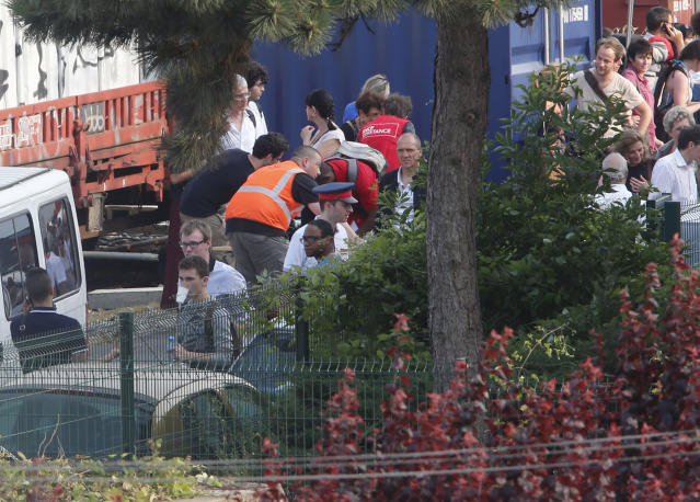 People are evacuated after a train derailed, in Bretigny sur Orge, south of Paris, Friday July, 12, 2013. A packed passenger train skidded off its rails after leaving Paris on Friday, leaving seven people believed dead and dozens injured as train cars slammed into each other and overturned, authorities said. (AP Photo/Jacques Brinon)