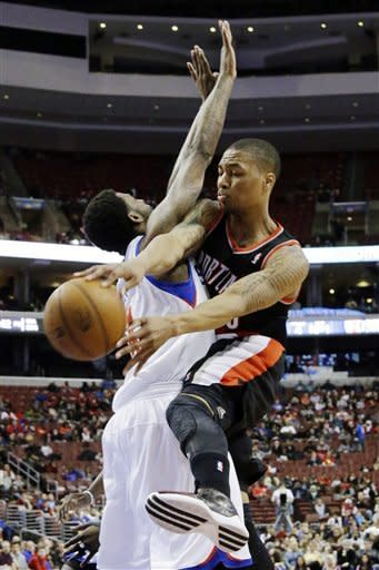 Portland Trail Blazers' Damian Lillard, right, fouls Philadelphia 76ers' Dorell Wright during the first half of an NBA basketball game, Monday, March 18, 2013, in Philadelphia. (AP Photo/Matt Slocum)