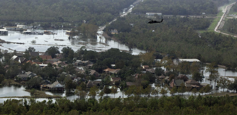 In this aerial photo, a Louisiana National Guard helicopter carries a sandbag to drop in an unintentional levee breach as it flies over the floodwaters in the aftermath of Hurricane Isaac in Braithwaite, La., Wednesday, Sept. 5, 2012. Thousands of electric customers are still without power, hundreds remained in shelters and several miles of coast line was tarred with weathered oil washing ashore, days after Isaac raked Louisiana. (AP Photo/Gerald Herbert)