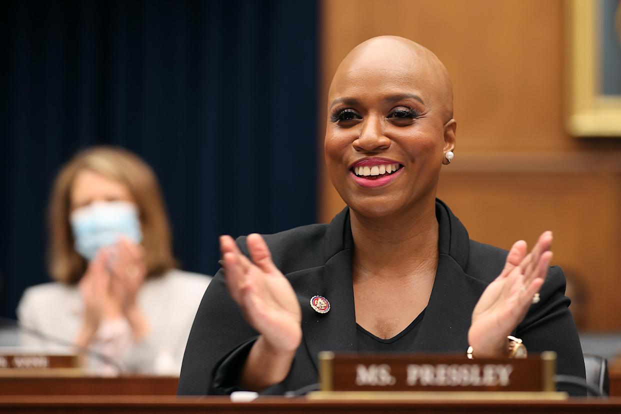 Ayanna Pressley smiles and applauds while seated behind a name plaque bearing her name.