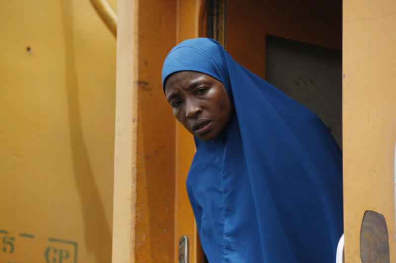 In this Photo taken, Friday, March . 8, 2013, a Muslim women peers out the door aboard an Ooni of Ife train to Kano, in Nigeria. Nigeria reopened its train line to the north Dec. 21, marking the end of a $166 million project to rebuild portions of the abandoned line washed out years earlier. The state-owned China Civil Engineering Construction Corp. rebuilt the southern portion of the line, while a Nigerian company handled the rest. The rebirth of the lines constitutes a major economic relief to the poor who want to travel in a country where most earn less than $1 a day. Airline tickets remain out of the reach of many and journeys over the nation's crumbling road network can be dangerous. The cheapest train ticket available costs only $13. ( AP Photo/Sunday Alamba)