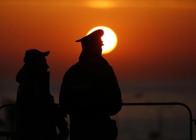 Olympic security personnel watch the sun set after the men's gold medal ice hockey game at the 2014 Winter Olympics, Sunday, Feb. 23, 2014, in Sochi, Russia. The game was the final competition of the winter games. (AP Photo/Petr David Josek)