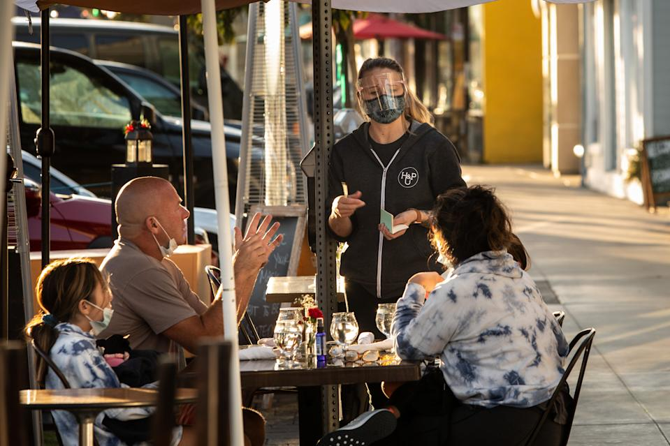 A masked and shielded server at The Hook & Plow, on Pier Avenue in Hermosa Beach, CA, takes and order on the final afternoon before a 10 p.m. end to outdoor dining because of the increase in COVID-19 cases, Wednesday, Nov. 25, 2020.  (Jay L. Clendenin / Los Angeles Times via Getty Images)