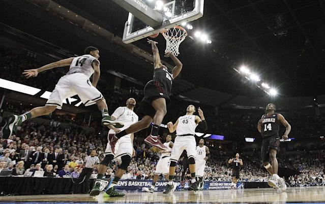 Harvard's Wesley Saunders (23) shoots against Michigan State's Gary Harris (14) in the second half during the third-round game of the NCAA men's college basketball tournament in Spokane, Wash., Saturday, March 22, 2014. Michigan State won 80-73. (AP Photo/Young Kwak)