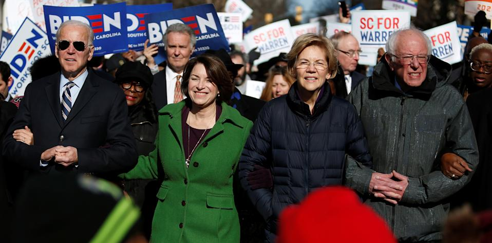 Seven of the Democratic U.S. Presidential candidates including former U.S. Vice President Joe Biden, Sen. Amy Klobuchar, Sen. Elizabeth Warren and Sen. Bernie Sanders, walk arm-in-arm with local African-American leaders during the Martin Luther King Jr. (MLK) Day Parade in Columbia, South Carolina on January 20, 2020.  (Randall Hill/Reuters)