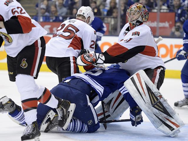 Ottawa Senators' Chris Neil (25) checks Toronto Maple Leafs' Mason Raymond (12) into Senators goalie Craig Anderson during the third period of an NHL hockey game in Toronto, Saturday, Feb. 1, 2014. (AP Photo/The Canadian Press, Frank Gunn)
