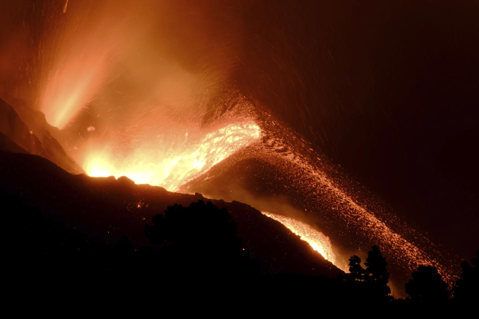 A volcano continues to spew out lava on the Canary island of La Palma, Spain in the early hours of Sunday, Oct. 10, 2021. A new river of lava has belched out from the La Palma volcano, spreading more destruction on the Atlantic Ocean island where molten rock streams have already engulfed over 1,000 buildings. The partial collapse of the volcanic cone has sent a new lava stream heading toward the western shore of the island. (AP Photo/Daniel Roca)