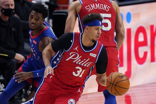 Philadelphia 76ers guard Seth Curry (31) drives as Detroit Pistons guard Delon Wright gives chase during the first half of an NBA basketball game, Saturday, Jan. 23, 2021, in Detroit. (AP Photo/Carlos Osorio)