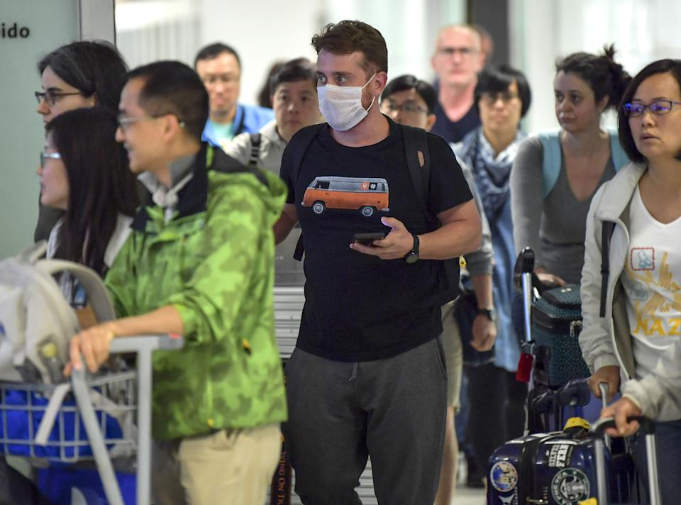 "A passengers, wearing a masks as a precautionary measure to avoid contracting the Covid-19 virus, travels through Guarulhos International Airport, in Guarulhos, Sao Paulo, Brazil on February 26, 2020. - The Brazilian Health Ministry confirmed Wednesday the diagnosis of coronavirus of a Brazilian resident in Sao Paulo, which became the first case of this epidemic in Latin America. The initial diagnosis ""was confirmed,"" Minister Luiz Henrique Mandetta said at a press conference in Brasilia. (Photo by NELSON ALMEIDA / AFP) (Photo by NELSON ALMEIDA/AFP via Getty Images)"