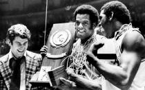 FILE - In this March, 1976, file photo, Indiana coach Bobby Knight, left, and team members Scott May, center, and Quinn Buckner, right, celebrate with the trophy after winning the NCAA Basketball Championship in Philadelphia in this Monday, March 30, 1976, file photo. They beat Michigan 86-68. The Indiana Hoosiers sat quietly inside their locker room on March 22, 1975. They knew what the first and only loss that season signified one perfect quest ended while another began. Minutes after losing 92-90 to archrival Kentucky in the Mideast Regional championship, the underclassmen vowed to come back the next season and go undefeated. They did. And 45 years later, the 1975-76 Hoosiers remain America's last perfect college basketball team. (AP Photo/File)