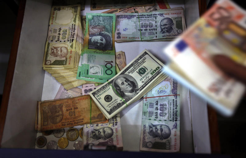 FILE - In this Thursday, Aug. 22, 2013 file photo, Indian and foreign currency notes lie in a drawer of a foreign currency exchange shop in Bangalore, India. From India to Indonesia, the currencies and stock markets of emerging economies have been roiled by speculation about when the U.S. Federal Reserve will start scaling back monetary stimulus that has kept interest rates ultra-low and sent investors to developing markets in search of higher returns. Separately, Asian economies that had been star performers are now in the dumps and the ebbing investment tide has sparked fears the region will suffer a rerun of its 1997-98 financial crisis. (AP Photo/Aijaz Rahi, File)