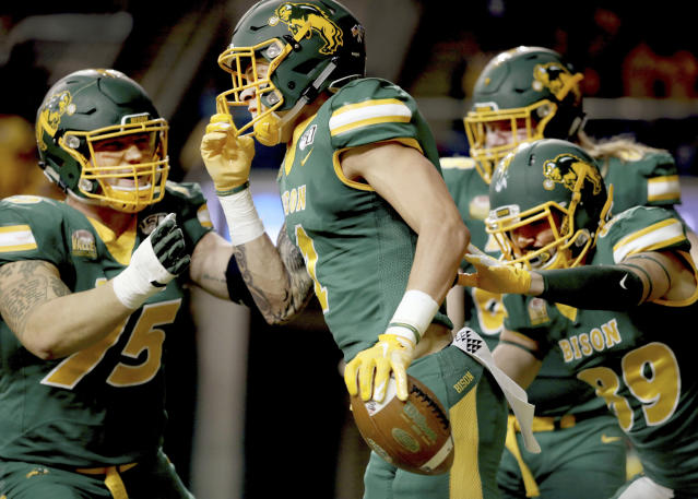 North Dakota State wide receiver Christian Watson, front, is mobbed by teammates after his long touchdown reception scores in the the first half of an FCS playoff NCAA college football game against Montana State, Saturday, Dec. 21, 2019, in Fargo, N.D. (AP Photo/Bruce Crummy)