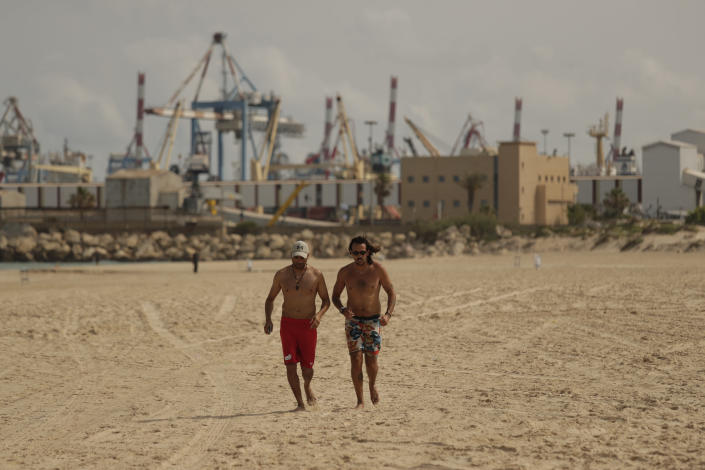 Men jog on the beach in the town of Ashkelon, Israel, Friday, May 21, 2021, aafter a cease-fire took effect between Hamas and Israel. The 11-day war between Israel and Hamas left more than 200 dead — the vast majority Palestinians — and brought widespread devastation to the already impoverished Hamas-ruled Gaza Strip. (AP Photo/Maya Alerruzzo)