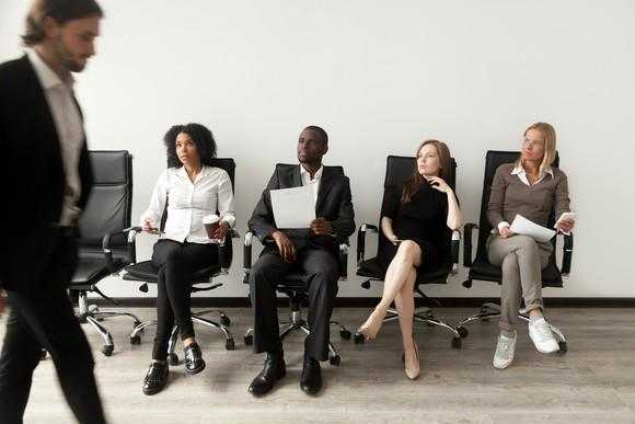 A man walking by four people sitting in chairs, as if they're job applicants.