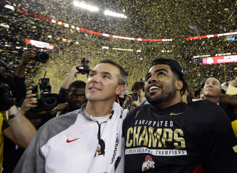 "FILE - In this Jan. 12, 2015, file photo, Ohio State head coach Urban Meyer, left, and Ezekiel Elliott celebrate after they defeated Oregon 42-20 in the NCAA college football playoff championship game in Arlington, Texas. Elliott apologized for the critical comments he made about play calling after the Michigan State game and says it was the wrong time to make it known he would not be returning to school next season. Elliott posted a long apology on Twitter on Monday, Nov. 23, 2015, saying, ""My intentions were not to point fingers at anyone for OUR failures."" (AP Photo/David J. Phillip, File)"
