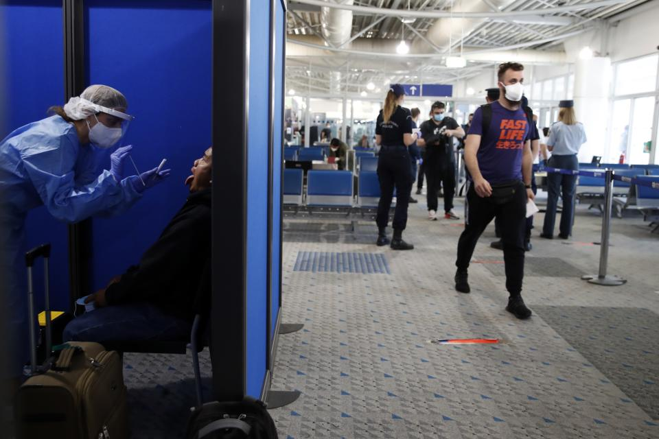 A medical staff conducts a test for the new coronavirus on the passengers who arrived from Doha, Qatar to the Eleftherios Venizelos International Airport in Athens, Monday, June 15, 2020. Greece is officially open to tourists as of Monday, with the first international flights expected into Athens and the northern city of Thessaloniki where passengers will not face compulsory COVID-19 tests. (AP Photo/Thanassis Stavrakis)
