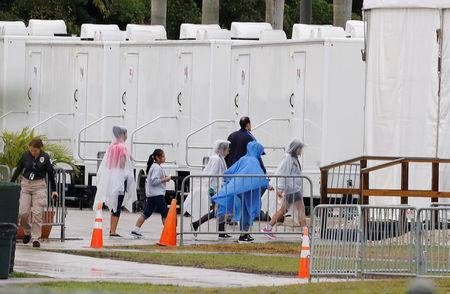 FILE PHOTO: Children and a security officer walk inside the Homestead Temporary Shelter for Unaccompanied Children, which is the Trump administration's largest shelter for migrant children, in Homestead, Florida, U.S, February 13, 2019. REUTERS/Joe Skipper