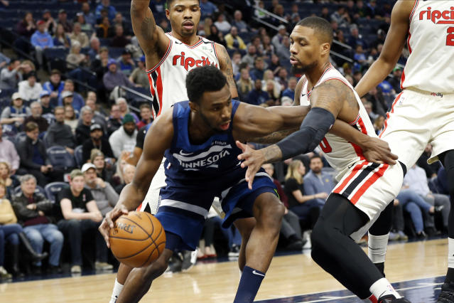 Minnesota Timberwolves' Andrew Wiggins, left, tries to drive around Portland Trail Blazers' Carmelo Anthony in the first half of an NBA basketball game Thursday, Jan. 9, 2020, in Minneapolis. (AP Photo/Jim Mone)