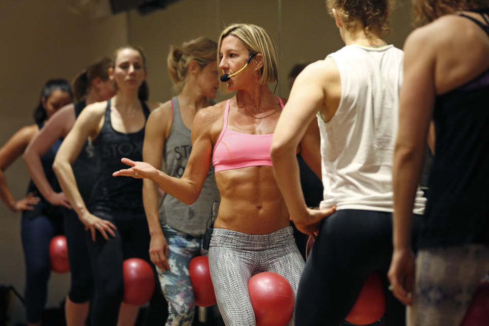 Women participate in a fitness class lead by Kira Stokes, center, at NYSC Lab in New York, Thursday, May 11, 2017. Some of the largest big box gyms including Equinox, Crunch and New York Sports Club, are opening small studios with high-end amenities, 'it' trainers and specialized workouts where consumers can pay per class in an effort to compete with boutiques. (AP Photo/Seth Wenig)