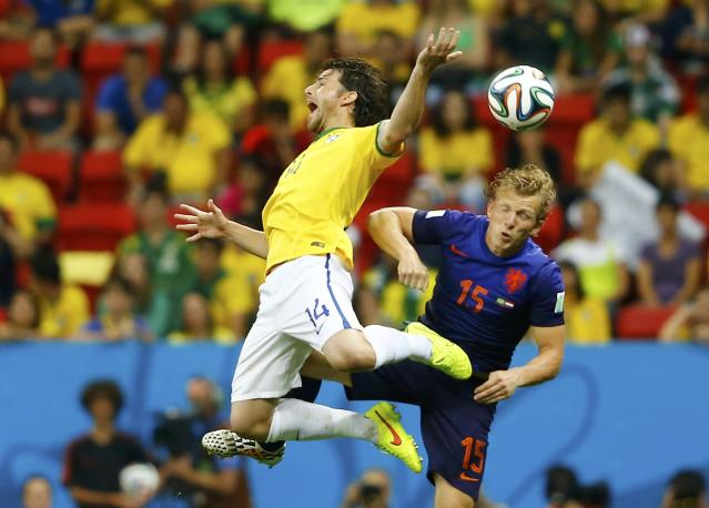 Brazil's Maxwell (L) and Dirk Kuyt of the Netherlands fight for the ball during their 2014 World Cup third-place playoff at the Brasilia national stadium in Brasilia July 12, 2014. REUTERS/Dominic Ebenbichler (BRAZIL - Tags: SOCCER SPORT WORLD CUP)