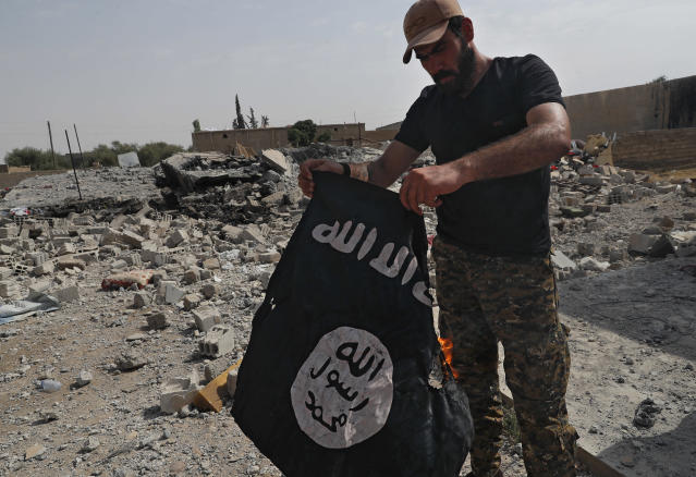 FILE - In this July 17, 2017, file photo, a fighter of the Christian Syriac militia that battles Islamic State group militants under the banner of the U.S.-backed Syrian Democratic Forces, burns an IS flag on the front line on the western side of Raqqa, northeast Syria. (AP Photo/Hussein Malla, File)