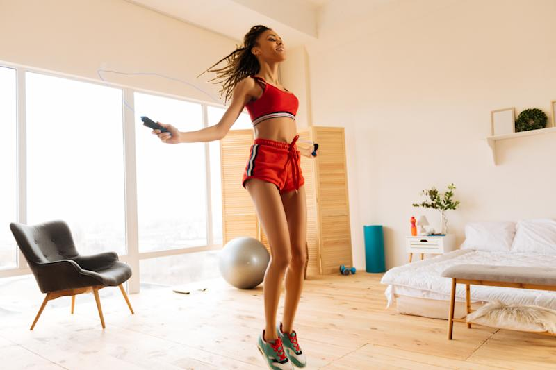 Skipping the rope. Fit woman wearing red shorts and top skipping the rope at home in the morning