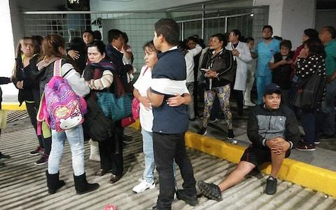 Patients and doctors of a hospital of Mexico City wait outside after the earthquake - Credit: EPA