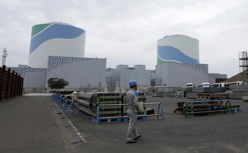 An employee of Kyushu Electric Power Co walks in front of reactor buildings at the company's Sendai nuclear power plant in Satsumasendai, Kagoshima prefecture, in this April 3, 2014 file photo. Satsumasendai never felt the earthquake that triggered the Fukushima nuclear disaster, some 1,600 kilometres to the north in March 2011. But residents saw their friends lose jobs and felt their future was threatened when the Sendai nuclear plant run by Kyushu Electric Power was idled along with the rest of Japan's reactors for a more stringent round of safety checks after Fukushima. To match JAPAN-NUCLEAR/RESTARTS REUTERS/Mari Saito/Files (JAPAN - Tags: POLITICS ENERGY ENVIRONMENT)