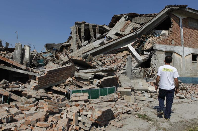 A man looks at a collapsed farm in Camposanto, northern Italy, Tuesday, May 29, 2012. A magnitude 5.8 earthquake struck the same area of northern Italy stricken by another fatal tremor on May 20. (AP Photo/Luca Bruno)