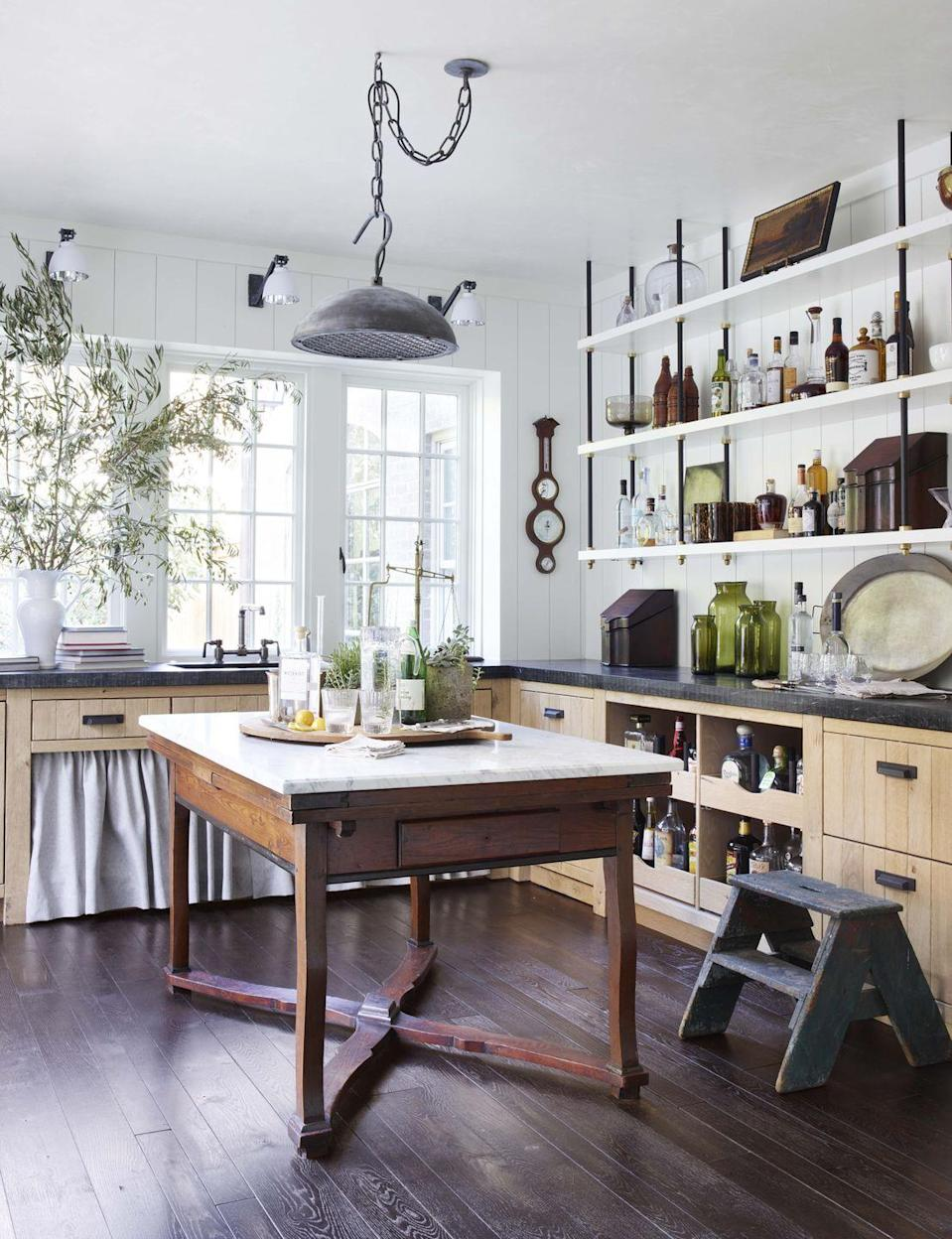 """<p>Wire-brushed French oak cabinetry, oiled soapstone counters, and suspended shelving with brass detailing bring charming utility to <a href=""""https://www.veranda.com/decorating-ideas/a28577679/amy-morris-atlanta-house-tour/"""" rel=""""nofollow noopener"""" target=""""_blank"""" data-ylk=""""slk:this Atlanta home's scullery, designed by Amy Morris and D. Stanley Dixon"""" class=""""link rapid-noclick-resp"""">this Atlanta home's scullery, designed by Amy Morris and D. Stanley Dixon</a>. Under-sink storage is concealed with a table skirt. Custom marble-top worktable, <a href=""""https://www.bdjeffries.com/"""" rel=""""nofollow noopener"""" target=""""_blank"""" data-ylk=""""slk:BD Jeffries"""" class=""""link rapid-noclick-resp"""">BD Jeffries</a></p>"""