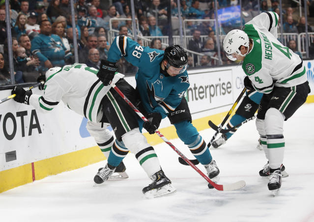 Dallas Stars defensemen Jamie Oleksiak, left, and Miro Heiskanen (4) battle for the puck with the San Jose Sharks center Tomas Hertl (48) during the first period of an NHL hockey game in San Jose, Calif., Saturday, January 11, 2020. (AP Photo/Josie Lepe)