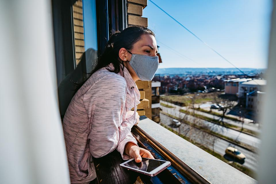 A woman looks out of a city window. She's wearing a cloth face mask.
