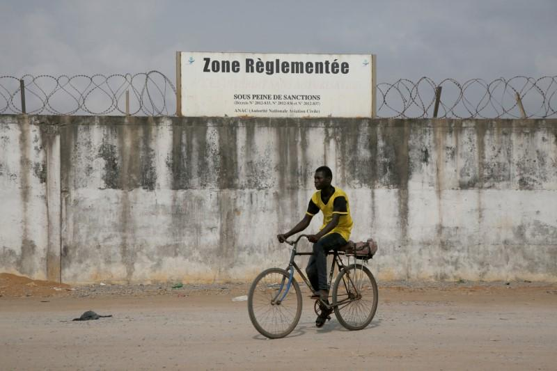 A cyclist drives pasts the wall of the Felix Houphouet Boigny airport in Abidjan