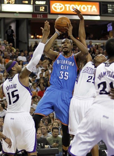 Oklahoma City Thunder forward Kevin Durant (35) shoots between Sacramento Kings' DeMarcus Cousins (15) and Travis Outlaw during the first quarter of an NBA basketball game in Sacramento, Calif., Friday, April 20, 2012. (AP Photo/Rich Pedroncelli)