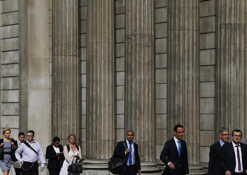 People walk past the Bank of England in London's City financial district, Monday, July 1, 2013. Canadian Mark Carney, the former head of the Bank of Canada and the first non-Brit to run the 319-year-old bank, moves into the bank's headquarters in the City of London on July 1. (AP Photo/Lefteris Pitarakis)
