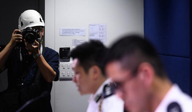 A photographer wears a protective helmet to a police press conference in protest of what journalists claimed was excessive force used against them at demonstrations. Photo: AFP