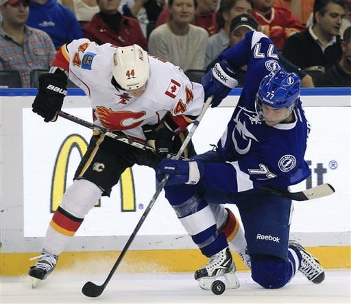 Calgary Flames defenseman Chris Butler (44) and Tampa Bay Lightning defenseman Victor Hedman (77), of Sweden, battle for the puck during the first period of an NHL hockey game on Thursday, Dec. 15, 2011, in Tampa, Fla. (AP Photo/Chris O'Meara)