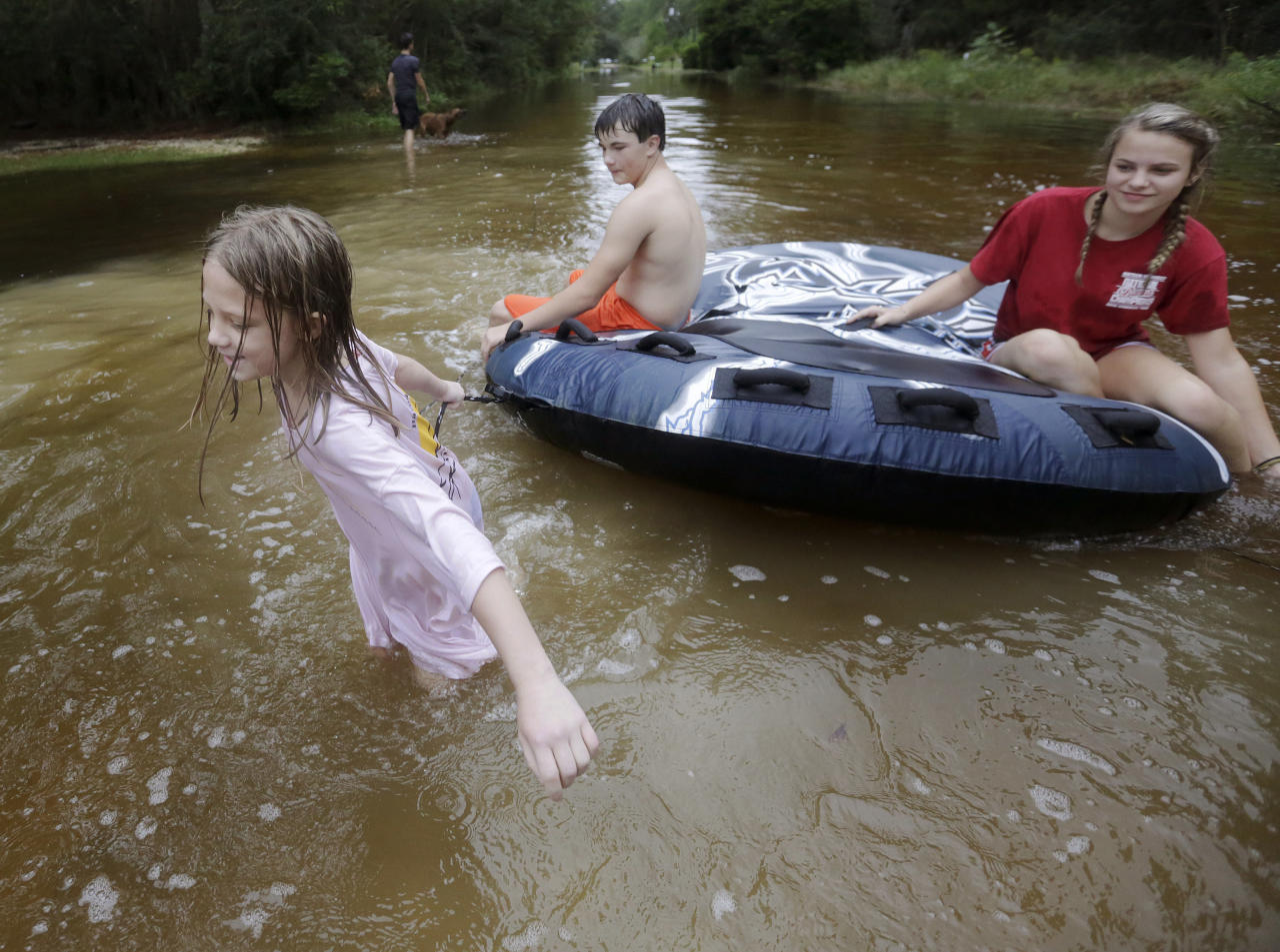 <p>Crimson Peters, 7, left, Tracy Neilsen, 13, center, and Macee Nelson, 15, ride in an inner tube down a flooded street after Hurricane Nate, Sunday, Oct. 8, 2017, in Coden, Ala. (Photo: Brynn Anderson/AP) </p>